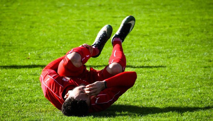 footballer lies on the pitch clutching head