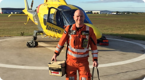 air ambulance doctor stands in front of helicopter