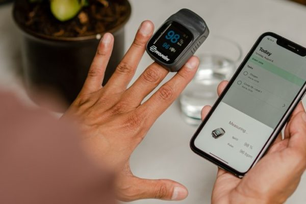 man wears a pulse oximetry device on his left middle finger to measure oxygen saturation, while holding a smartphone in his right hand